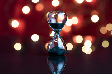 Hourglass or sandglass on red dark background with decoration light bokeh using as Party always end concept