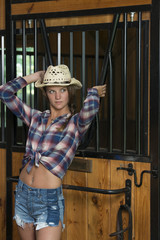 Beautiful teen girl poses in cowgirl gear in barn holding riding gear (tack)