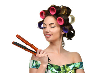 Woman with curlers hold hair curling ironing tool
