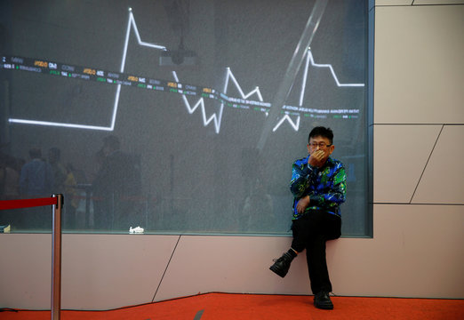 A man sits inside trading floor of the Indonesia Stock Exchange building in Jakarta