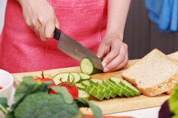 hand cutting cucumber on board in kitchen room