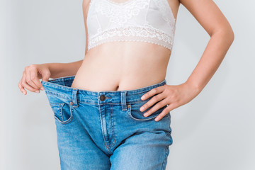 Young woman showing successful weight loss with her jeans, Healthcare, Diet concept