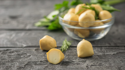 Smoked mozzarella cheese in a glass bowl with herbs on a wooden table.