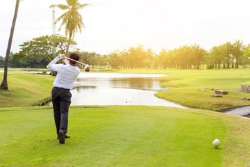 young asian businessman playing golf on the beautiful golf course in the morning with sunbeam at summer time.