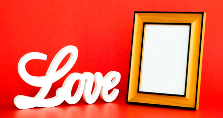 white LOVE sign in cursive letters on a red background with an empty picture frame to customize