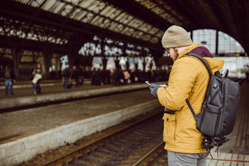 man stands on the railway station look into smartphone