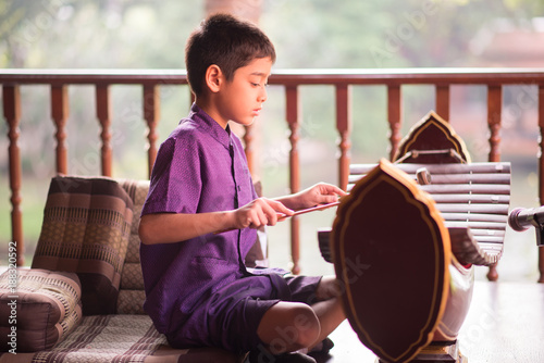 Little asian Thai boy playing alto xylophone music