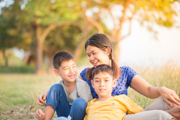 Asian single mom having fun with her sons together in the park