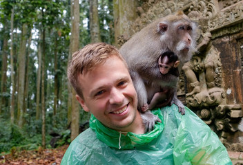 Caucasian tourist in green raincoat with wild monkey on his shoulder
