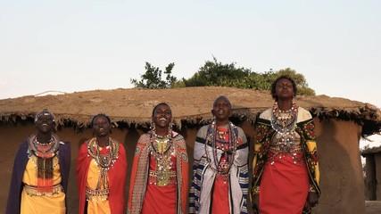 Wall Mural - wide shot of five maasai women in traditional dress singing and dancing in a village near maasai mara, kenya