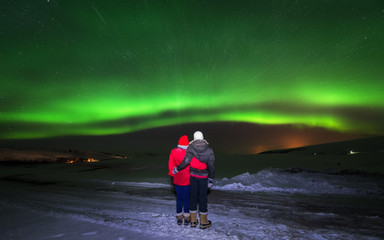 couple holding each other standing looking at the stunning aurora in the night sky of Iceland