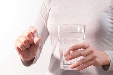 isolate of the women hand holding the medicine with a glass of water, medicine recovery concept