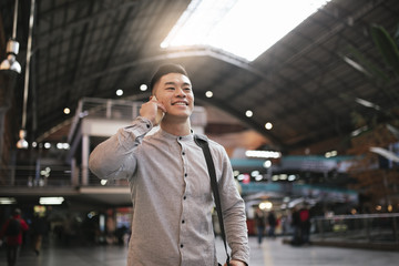 Handsome asian man using mobile in the train station.