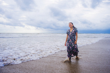 portrait of young beautiful and happy Asian Chinese woman on her 20s or 30s wearing long chic dress walking alone on beach sea water enjoying