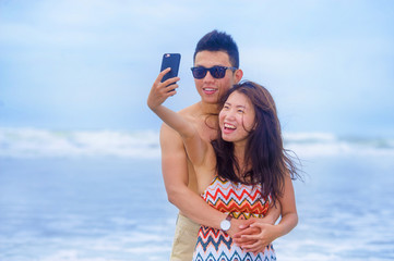 young happy and beautiful Asian Chinese couple taking selfie photo with mobile phone camera smiling joyful having fun on the beach