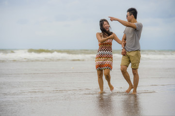 young beautiful Asian Chinese couple walking together on the beach happy in love enjoying holidays and relax smiling joyful in romance concept