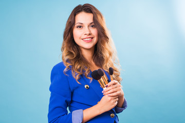Young make-up artist with brushes on blue background