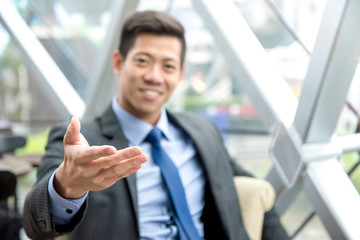 Friendly Asian businessman reaching out hand with open palm, welcome gesture