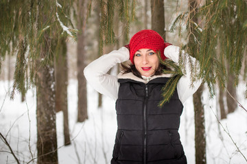 Girl in a red cap and warm jacket in the forest in a winter