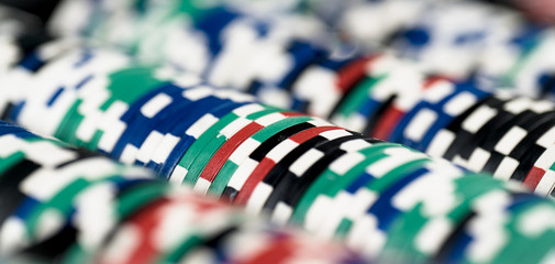 High contrast image of casino roulette and poker chips on bokeh background.