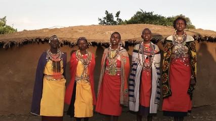 Wall Mural - panning shot of five maasai women singing in a village near mara, kenya