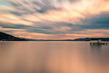 A long exposure of the sunset lighting up the cloudy sky over Lake Washington Wall mural