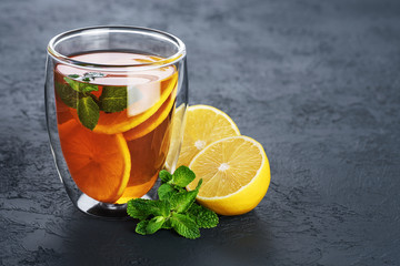 Hot tea with mint and lemon in a glass with double walls on a dark background.