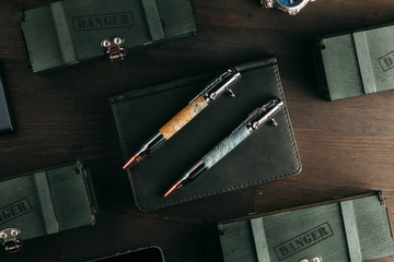 set of expensive military pens in wooden boxes, compositions on a dark background with attributes