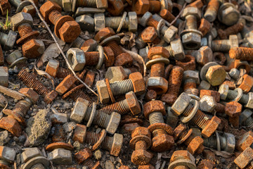 Rusty bolts and nuts on the floor in the sunlight