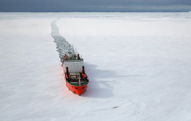 Scientific research vessel, breaks its way in the ice of the Antarctic. View from above.