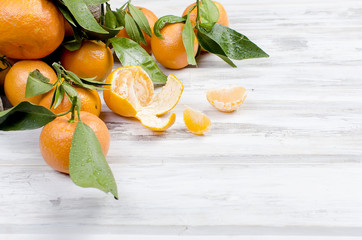 Tangerines clementine with leaves on a wooden table.