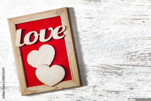 Valentine\'s Day. A word of love in a decorative frame and two hearts ...