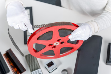 hands woman holding red reel 16mm film