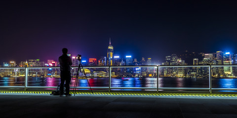 Fotomurales - Man taking photo for the beautiful night view of Victoria Harbor of Hong Kong
