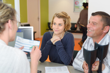 expectant couple talking while counsulting doctor in clinic