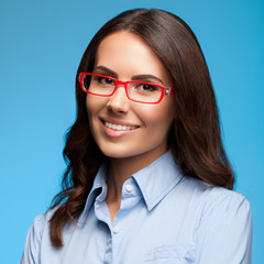 Cheerful businesswoman in glasses, on blue background