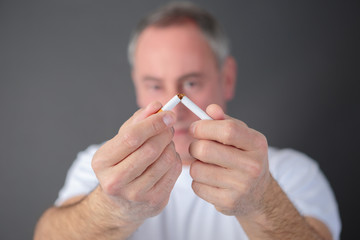 sadult man breaking cigarette
