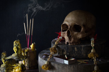 Still Life image of incense and candle with smoke and skull in room with has dim light