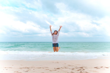 A woman jumping on the beach in front of the sea with feeling happy and freedom