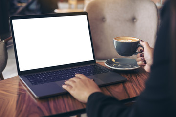 Mockup image of a businesswoman using laptop with blank white desktop screen while drinking hot coffee on wooden table in cafe