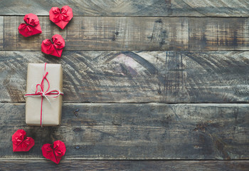 Red paper hearts with gift on wooden background, Valentines Day. Space to copy. Top view