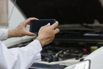 Hands of mechanic man taking a picture with mobile smart phone against car in open hood at the repair garage.
