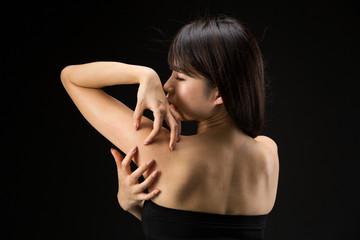 背中を掻く女性