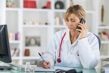 cheerful female doctor on phone at office