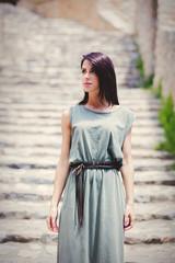 Woman in green gress waking down stairs on Greece street
