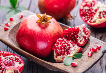 Ripe pomegranate fruits on the wooden background.