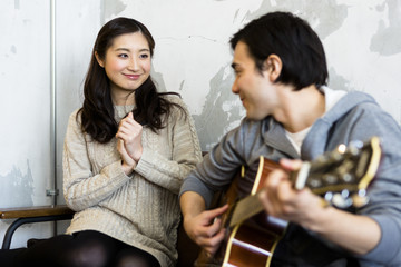 ギターを弾く男性とそれを聴く女性