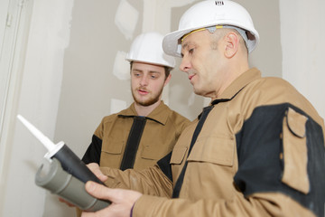 mentor showing usage of caulking to his apprentice