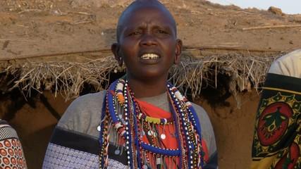 Wall Mural - close up of a maasai woman wearing grey clothing and traditional jewellery singing in a village near masai mara in kenya