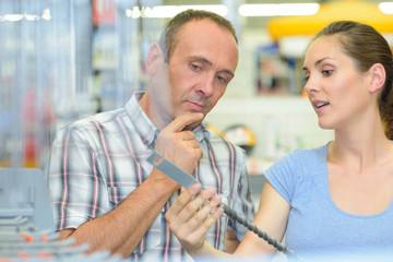 Couple looking at long drill bit